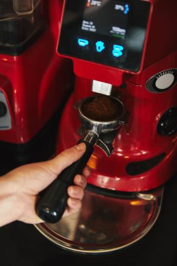 Close-up partial view of barista preparing espresso in coffee machine stock vector