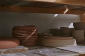 keramické misky a jídla na dřevěných policích ve studiu keramiky