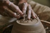 Fotografie selective focus of professional potter decorating clay pot at workshop