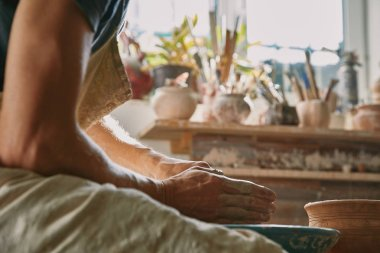 selective focus of professional potter working with clay at potter studio