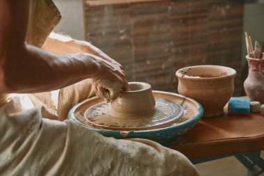 cropped image of professional potter working on pottery wheel at workshop