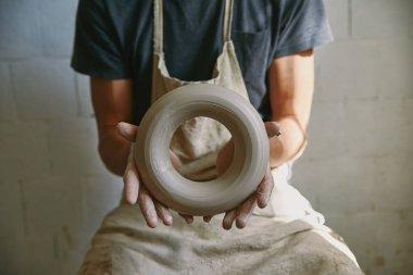 selective focus of professional potter in apron holding clay at pottery studio