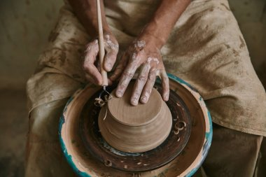 partial view of professional potter decorating clay pot at workshop