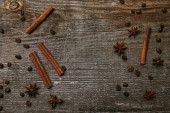 top view of cinnamon sticks with anise and coffee beans on rustic wooden table