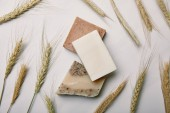 Fotografie top view of various handmade soap with wheat on white marble surface