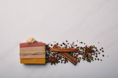 top view of handmade soap with anise, coffee beans and cinnamon sticks on white marble surface