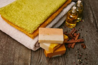 close-up shot of soap pieces with stacked towels, spices and massage oil on rustic wooden tabletop