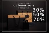 Nahaufnahme von Einkaufstaschen auf schwarzem Hintergrund mit Herbstschlussverkauf mit 30, 50, 70 Prozent Rabatt