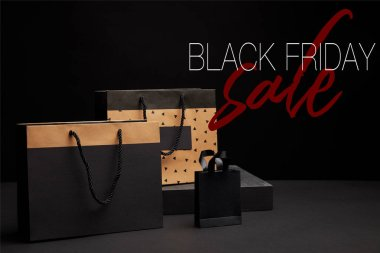 close up view of shopping bags arranged on black background with black friday sale