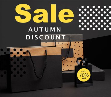 close up view of shopping bags arranged on black background with autumn sale discount with 70 percents