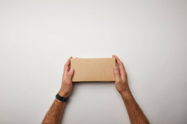 cropped image of man holding delivery food box on white surface