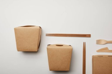 elevated view of arranged wok boxes, chopsticks and disposable knife with fork on white surface