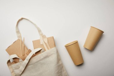 flat lay with cotton bag with food boxes and two disposable coffee cups on white surface