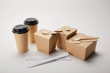 disposable fork with knife, chopsticks, paper coffee cups and cardboard food boxes on white