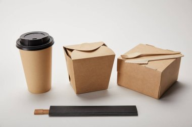 close up view of paper coffee cup, food boxes and chopsticks on white