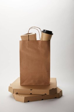 pizza boxes and food delivery paper bag with disposable coffee cup and wok box on white