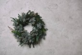 round fir wreath for Christmas decoration hanging on grey wall in room