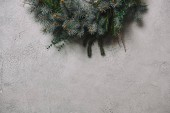 Fotografie cropped image of fir wreath for Christmas decoration hanging on grey wall in room