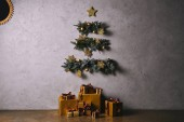 ručně vyráběné vánoční stromeček visí na šedou stěnu, dárkové krabice na podlaze v pokoji