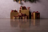 Fotografie surface level of Christmas gift boxes on floor under christmas tree in room