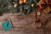 pohled shora Vánoční dárková krabička, věnec jedle, stuha cívky a obálky na dřevěný stůl
