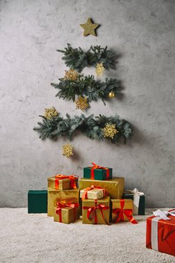 handcrafted Christmas tree hanging on grey wall, gift boxes on floor in room