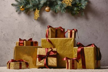 Pile of golden Christmas gift boxes on carpet in room under christmas tree stock vector