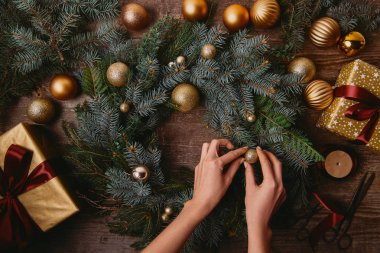 cropped image of woman making christmas decoration at wooden table