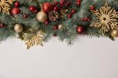 pohled shora na větvičky jedle s vánoční hračky a zlaté vločky izolované na bílém