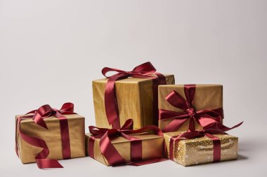 Christmas gift boxes with burgundy ribbons isolated on white