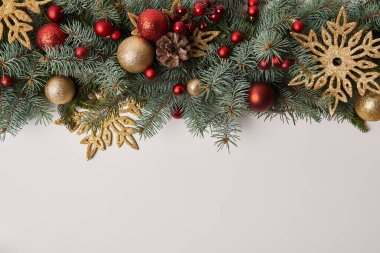 top view of fir twigs with Christmas toys and golden snowflakes isolated on white