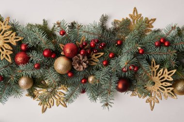 top view of fir twigs with colored Christmas decoration isolated on white