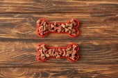 top view of two plastic bones full of dog food on wooden background