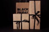 zabalené dárkové krabičky a černý pátek nákupní taškou na černém povrchu