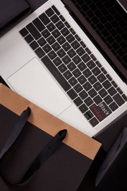 top view of laptop with black friday button on keyboard and shopping bag on black