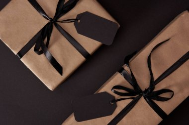 top view of craft wrapped gift boxes with black tags on black surface, black friday concept