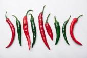 pohled shora na červené a zelené chilli papričky v řadě na bílé mramorové stolní