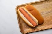 pohled shora na hot dog na dřevěné desce na bílý mramor povrch