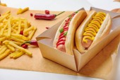 Fotografie close-up shot of spicy hot dogs with french fries on parchment paper