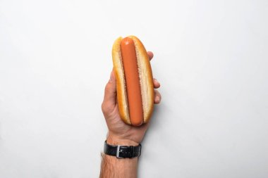 cropped shot of man holding tasty hot dog on white marble surface