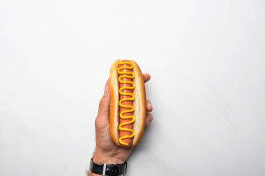 cropped shot of man holding tasty hot dog poured with mustard on white marble surface