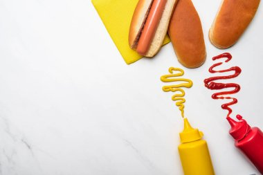 top view of tasty hot dog with mustard and ketchup on white marble surface
