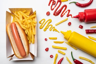 top view of hot dog and fries with mustard and ketchup on white surface