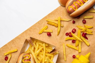 top view of tasty french fries with hot dogs on parchment paper isolated on white