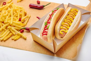Close-up shot of delicious hot dogs with french fries on paper stock vector