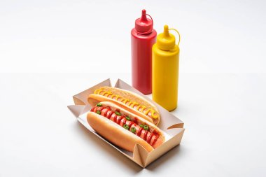 Close-up shot of delicious hot dogs with mustard and ketchup on white stock vector