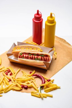 Close-up shot of spicy hot dogs with french fries, mustard and ketchup on paper on white surface stock vector
