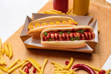 close-up shot of hot dogs with french fries on paper on white surface