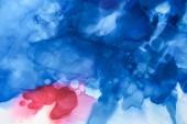tmavě modré, červené a fialové cákance barev alkoholu jako abstraktní pozadí