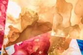 hnědé a červené cákance barev alkoholu na listy papíru jako abstraktní pozadí
